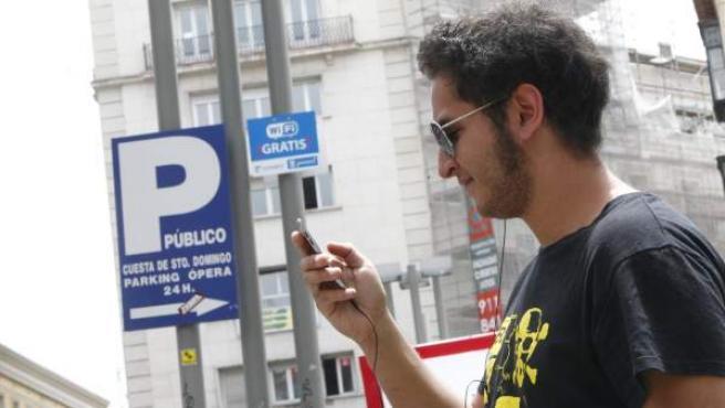 Un usuario conecta su teléfono móvil a la red wifi de la Plaza de Santo Domingo de Madrid.