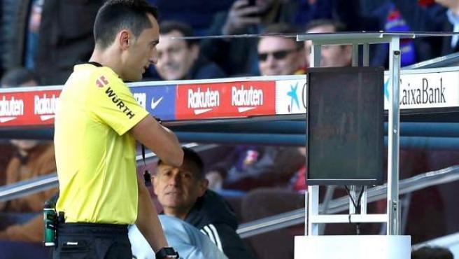 El árbitro murciano Sánchez Martínez consulta el VAR antes del penalti del segundo gol del Barcelona en el Camp Nou.