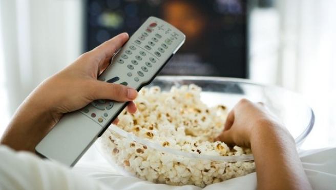 Una persona cambia canales de la televisión con el mando a distancia.