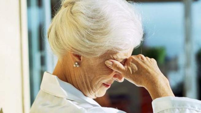 Una anciana se cubre el rostro.