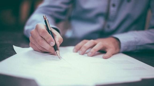 Imagen de archivo de un hombre firmando un contrato.