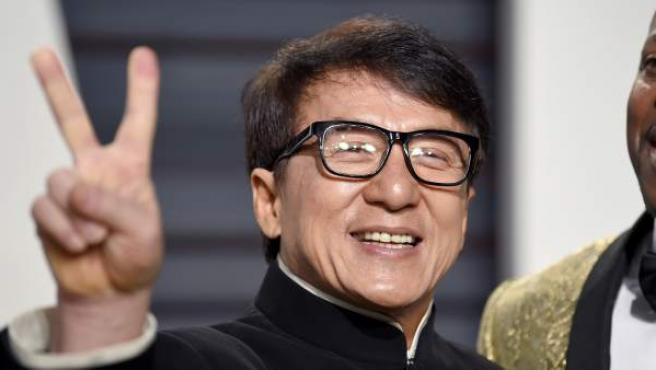 Jackie Chan saluda a su llegada a la Vanity Fair Oscar Party.