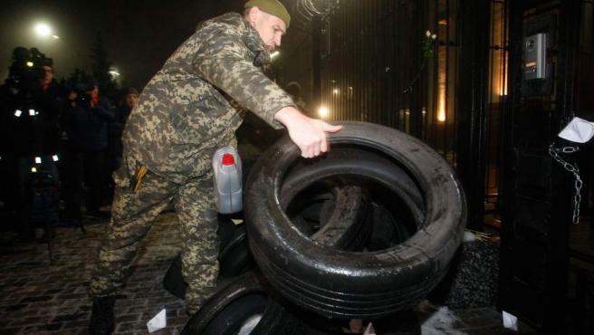 Un protestante coloca neumáticos durante una concentración cerca de la embajada rusa en Kiev (Ucrania).