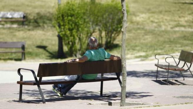 Un hombre sentado en un banco en un parque.