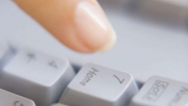 Una mujer presionando un teclado de un ordenador.