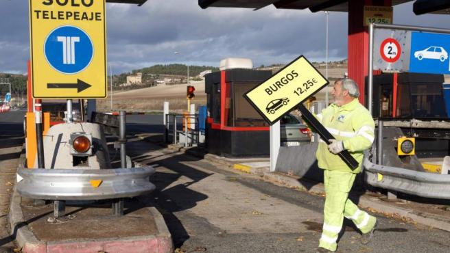 Un operario retira la señalización del peaje alavés de Armiñón de la autopista AP-1.
