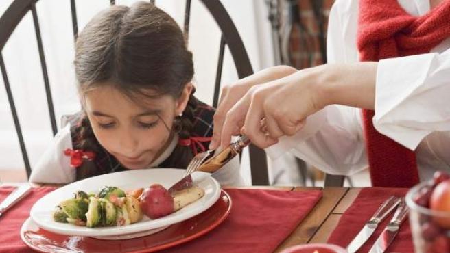Una madre corta la comida de una niña.