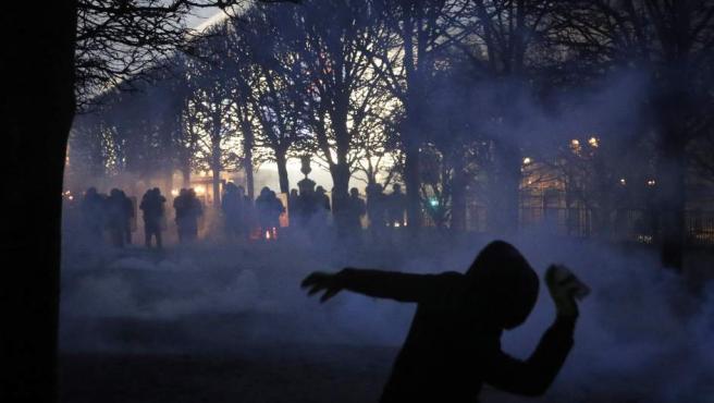 Un manifestante de los 'chalecos amarillos' arroja cócteles molotov a agentes antidisturbios de la Policía francesa.