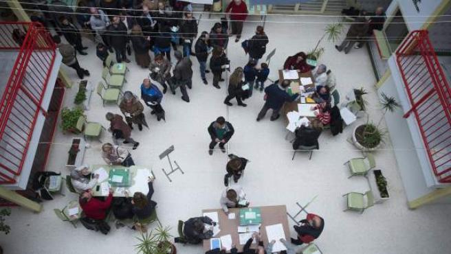 Numerosos ciudadanos haciendo cola antes de votar en las elecciones autonómicas para la Junta de Andalucía, en un colegio de Málaga.