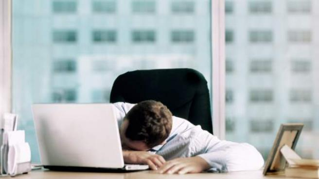 Un hombre, exhausto frente a su ordenador.