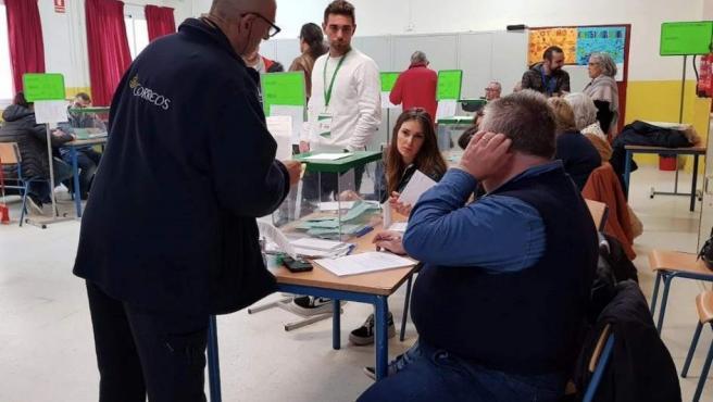 Un funcionario entrega votos que han llegado por correo y deben estar en la mesa electoral hasta que se abran, en el colegio Sor Ángela de la Cruz del distrito Macarena, en Sevilla.
