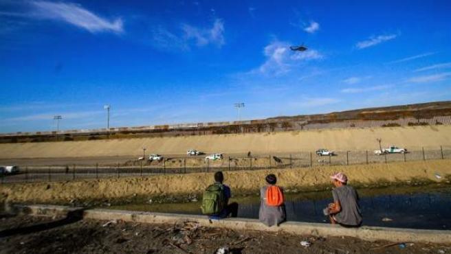 Integrantes de la caravana migrante de centroamericanos, en Tijuana, México, junto a la valla de la frontera con EE UU.