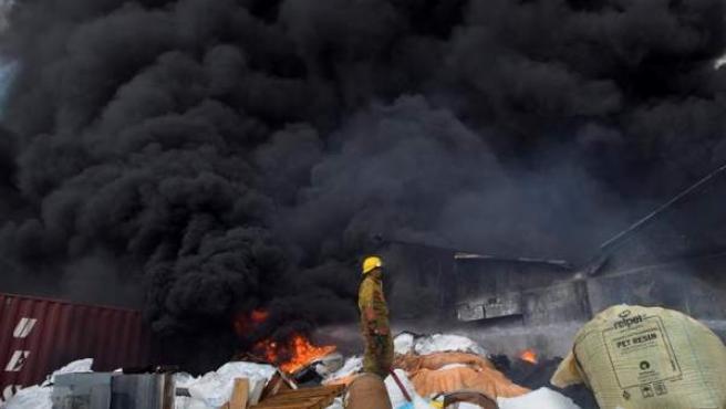 Un bombero solicita ayuda tras quedarse sin agua entre los escombros que dejó una fuerte explosión en una fabrica de plásticos en Santo Domingo, República Dominicana.