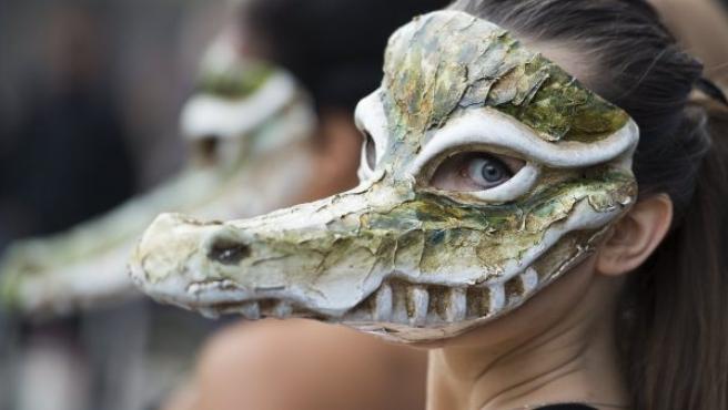Una activista cubre su cara con una máscara de cocodrilo, durante una protesta de PETA en la Semana de la Moda de Londres.