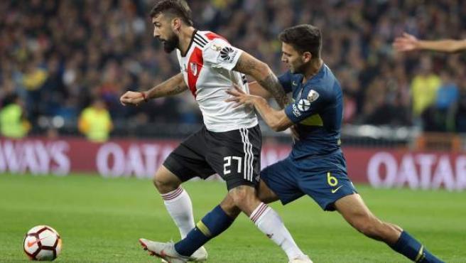 El jugador del River Plate, Lucas Pratto (i) lucha por un balón con Lisandro Magallán, del Boca Juniors.