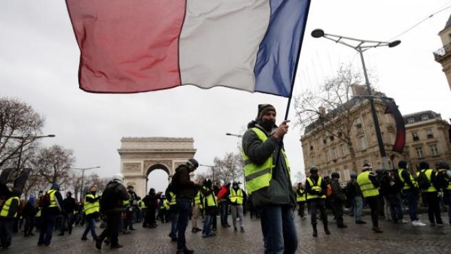 Un hombre con chaleco amarillo porta una bandera francesa durante una manifestación en los Campos Elíseos de París.