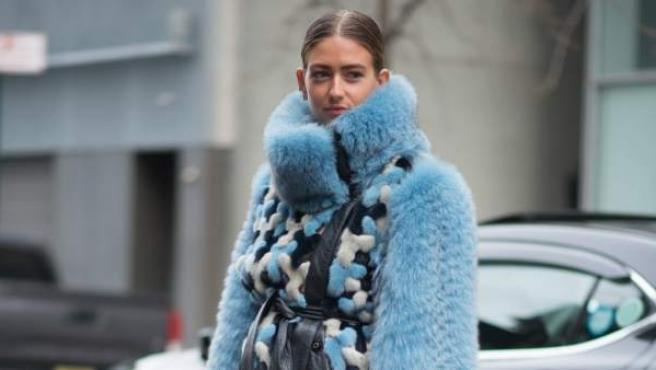 La estilista Emili Sindlev con un abrigo de pelo azul durante la Semana de la Moda de Nueva York.