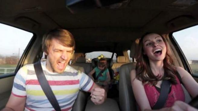 Una pareja con sus hijos cantan mientras van en el coche.