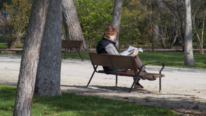 Una mujer leyendo en un banco del parque madrileño de El Retiro.