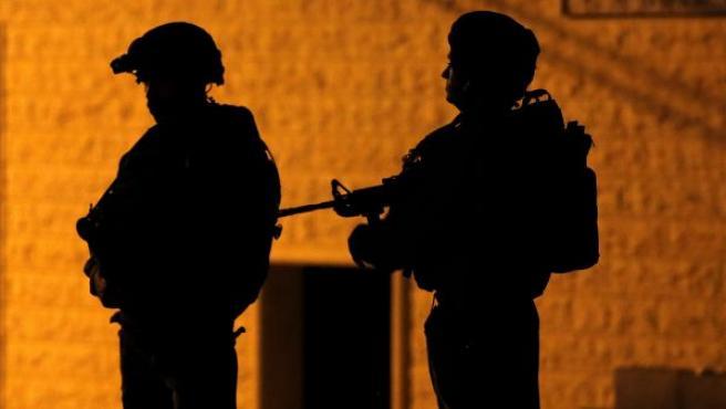 Soldados del ejército israelí patrullan, en en Yata, al sur de Hebron (Cisjordania), durante una operación militar tras un ataque en Tel Aviv que dejo cuatro muertos.