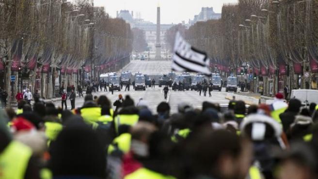 La policía bloquea en los Campos Elíseos a los manifestantes de los chalecos amarillos.