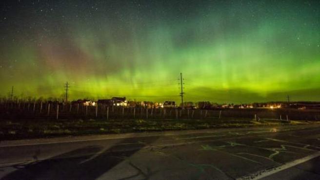 Imagen de una aurora boreal (alteración de la ionosfera) sobre una población.