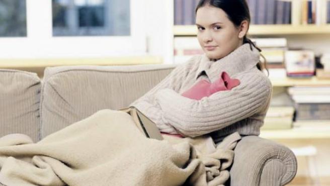 Una mujer, en el sofá de casa, se tapa para combatir el frío.