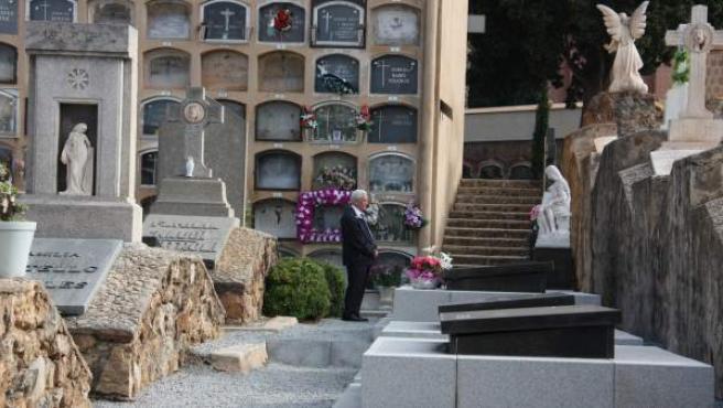 Un hombre frente a una tumba en el cementerio de Les Corts de Barcelona.