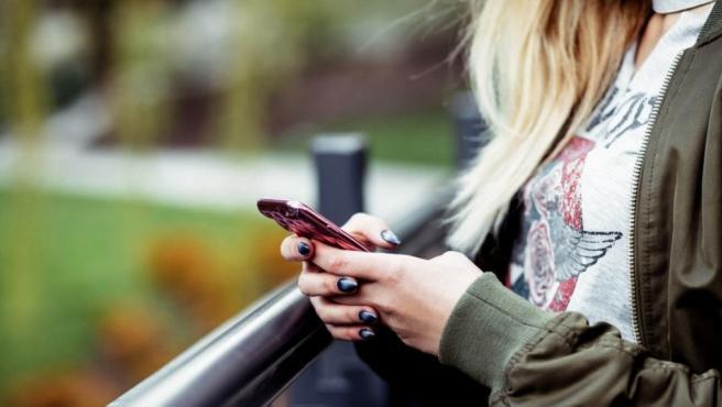 Una chica utiliza su teléfono móvil.