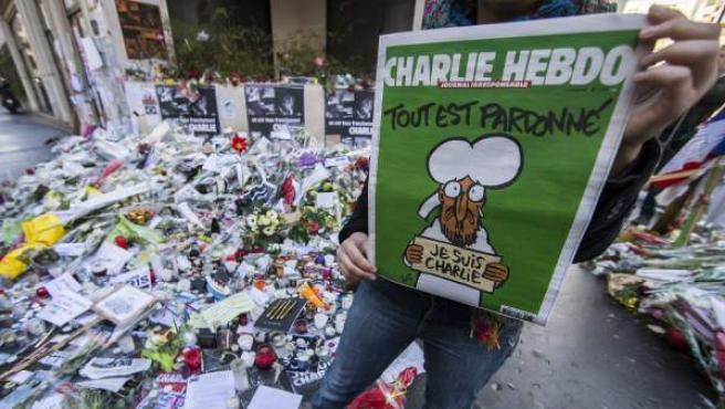 Un hombre sostiene una publicación del semanario satírico 'Charlie Hebdo' tras el atentado.