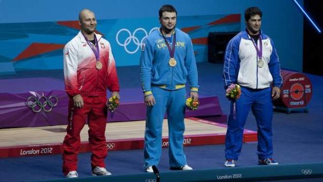 El ucraniano Oleksiy Torokhti, en el centro, con la medalla de oro de halterofilia en la categoría de 105 kilos, en los Juegos de Londres 2012.