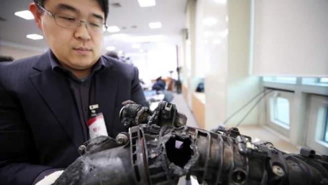 Un funcionario del Ministerio de Transporte de Corea del Sur examina los daños en la válvula de recirculación de gases de escape de un vehículo BMW cuyo motor se incendió, en Seúl.