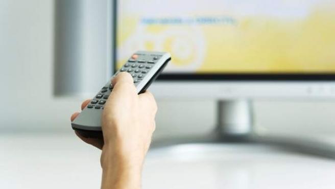 Un televidente maneja el mando a distancia.