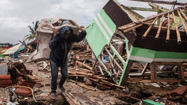 Un hombre recoge pertenencias entre los escombros.