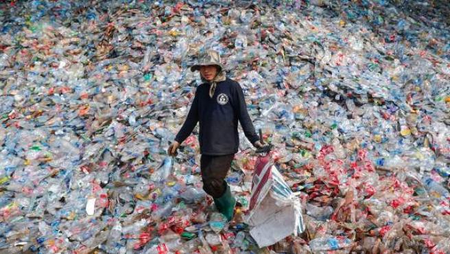 Un trabajador camina entre montañas de botellas de plástico en una planta de reciclaje de Samut Sakhon, afueras de Bangkok, Tailandia.