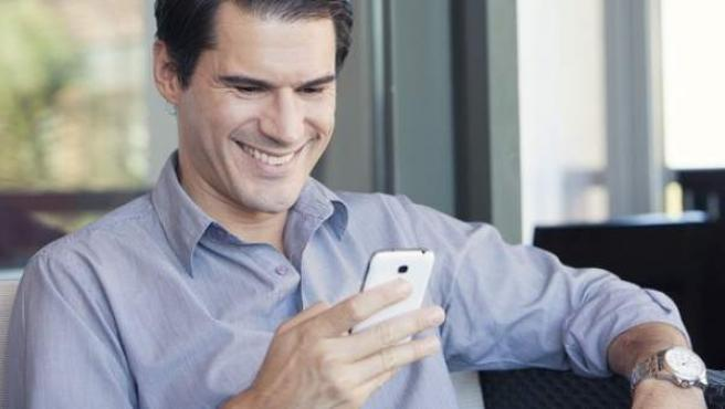 Un hombre observa la pantalla de su teléfono móvil.