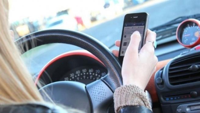 Mujer al volante con el móvil.