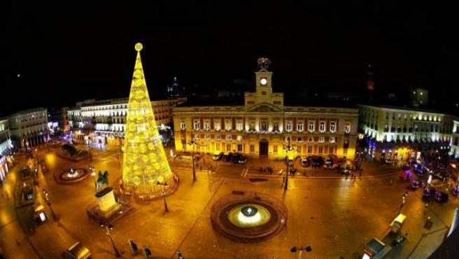 Combo de fotografías del reloj de la Puerta del Sol vacío y lleno de gente que como es habitual dio la bienvenida al nuevo año en una celebración que concentró a miles de personas en la popular plaza madrileña.