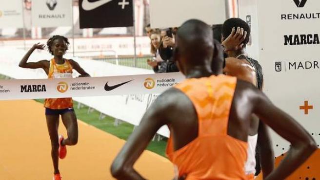 La keniana Brigid Kosgei (i), entra como vencedora de la San Silvestre Vallecana, ante la mirada del vencedor masculino.