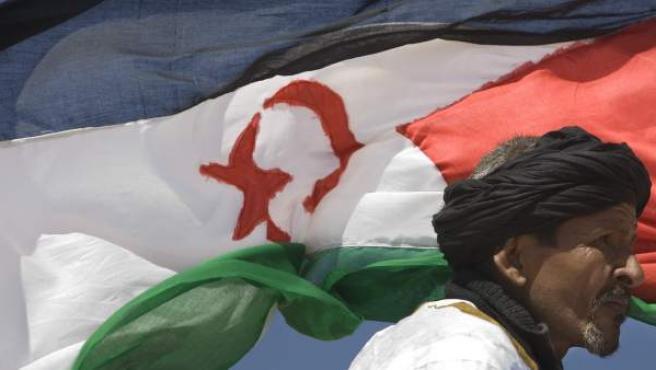 Un defensor del Frente Polisario pasa junto a una bandera del Sáhara Occidental.