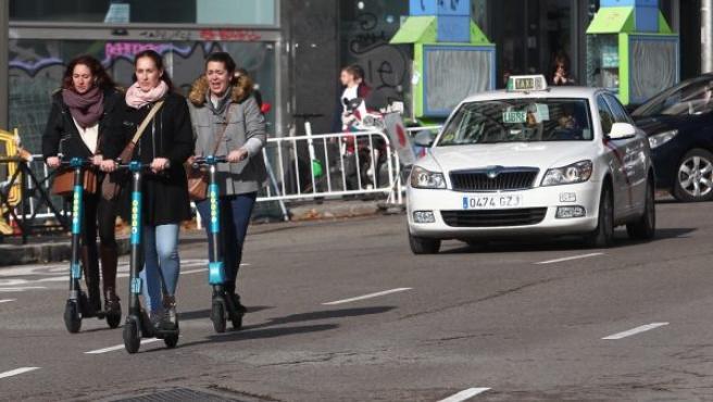 Tres jóvenes circulan en patinete, por una de las calles del centro de la capital.