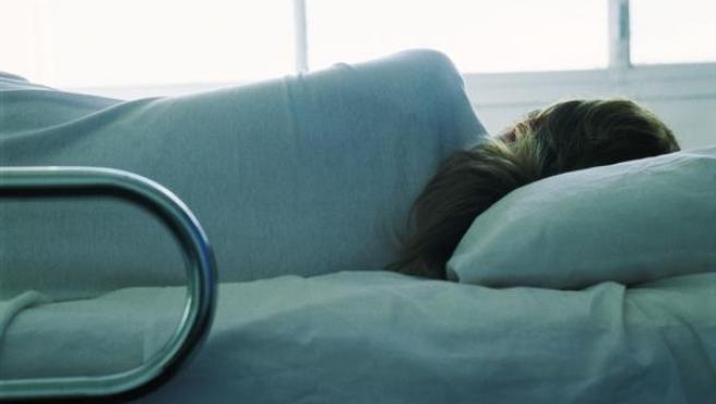 Una mujer en una cama de hospital.