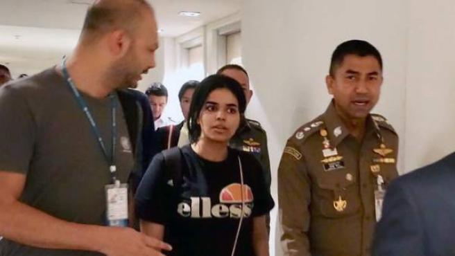 La joven saudí, Rahaf Mohammed Al-Qunun (en el centro), con el jefe de la policía de inmigración de Tailandia y un trabajador de ACNUR.