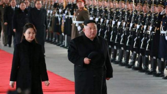 El líder norcoreano, Kim Jong-un, y su esposa, Ri Sol-ju, pasan revista a una guardia de honor antes de su salida hacia China desde Pyongyang, Corea del Norte.