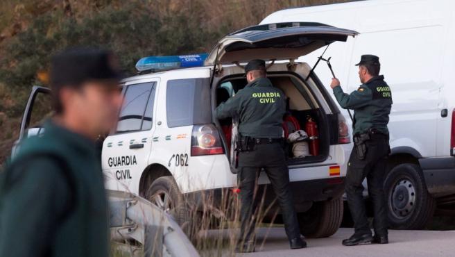 Dos guardias civiles sacan equipos de un vehículo en las inmediaciones del pozo donde ha caído un niño de dos años, en Totalán (Málaga).