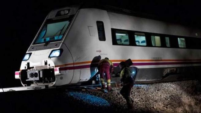 Operarios trabajan en el tren de la línea Madrid-Zafra que descarriló a 500 metros de la estación de Torrijos (Toledo), sin que se registrasen heridos.