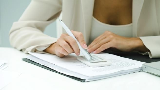 Una mujer calculando el pago de sus impuestos.