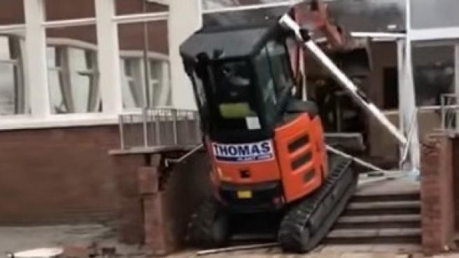 Un obrero destruye la entrada de un hotel de Liverpool con una excavadora.