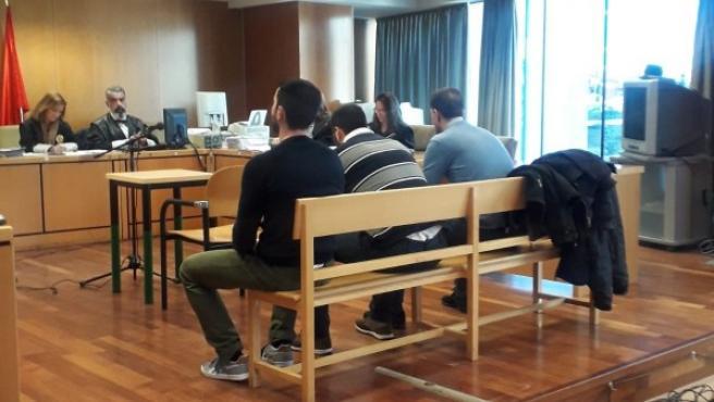 Los tres acusados de violar en grupo a una chica de dieciocho años sentados en el banquillo durante el juicio.