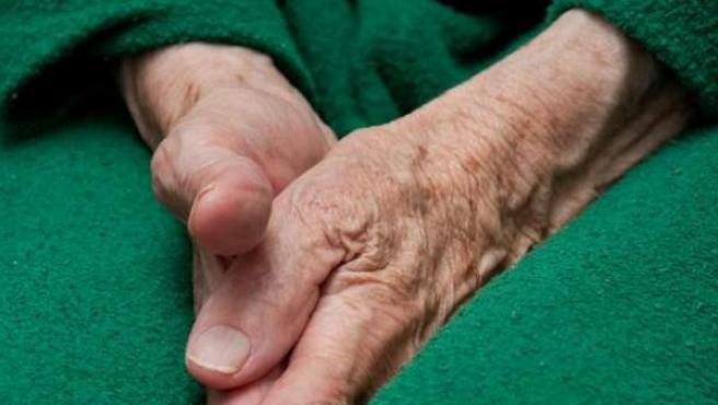 Las manos de una mujer mayor, descansando sobre sus piernas.